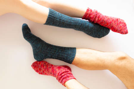 Top view of two pairs of legs wearing a red and a blue sock on white background Reklamní fotografie