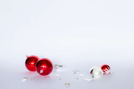 Broken red and silver Christmas baubles lying on white background