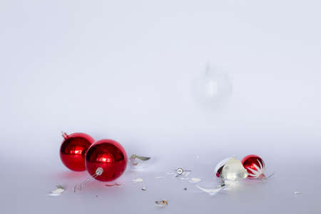 Falling and broken red and silver Christmas baubles on white background
