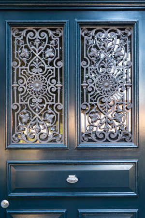 Dark blue painted wooden door with intricate ornate window grate and silver colored door handle Stock Photo