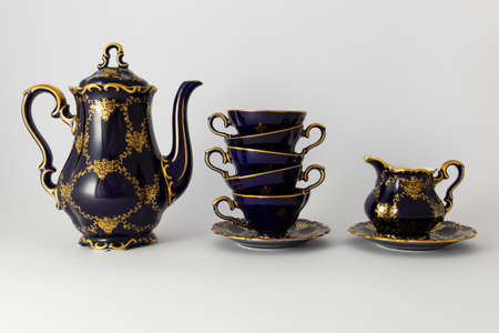 Closeup of a beautiful cobalt blue colored vintage porcelain tea set with golden floral pattern on white background. The set includes a tea pot, a milk jug and a stack of tea cups. Stockfoto