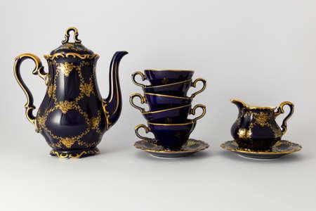Primer plano de un hermoso juego de té de porcelana vintage de color azul cobalto con estampado de flores dorado sobre fondo blanco. El juego incluye una tetera, una jarra de leche y una pila de tazas de té. Foto de archivo