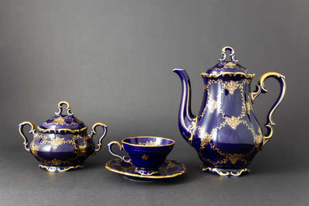 Closeup of a beautiful cobalt blue colored vintage porcelain tea set with golden floral pattern on dark gray background. The set includes a tea pot, a sugar bowl and a tea cup.