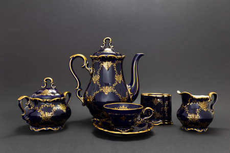 Closeup of a beautiful cobalt blue colored vintage porcelain tea set with golden floral pattern on dark gray background. The set includes a tea pot, a sugar bowl, a milk jug and a tea cup.