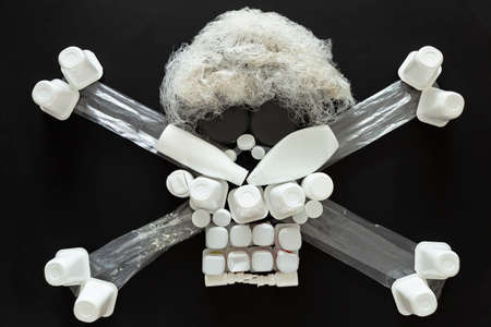 Concept of environmental pollution with plastic waste. Top view of a jolly roger or skull and crossbones symbol made with different plastic objects. 版權商用圖片