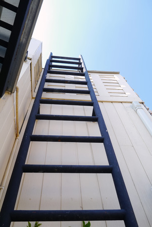 working stiff: fixed ladder to blue blue sky. Stock Photo