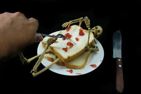 Human skeleton sanwich dinner halloween night on black background.