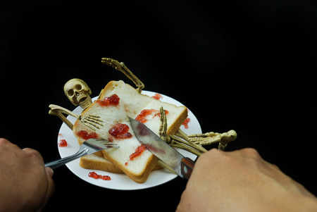 Human skeleton sanwich dinner halloween night on black background.