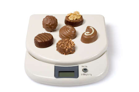 Scale with chocolate isolated over a white background. Check other photos in the serie.