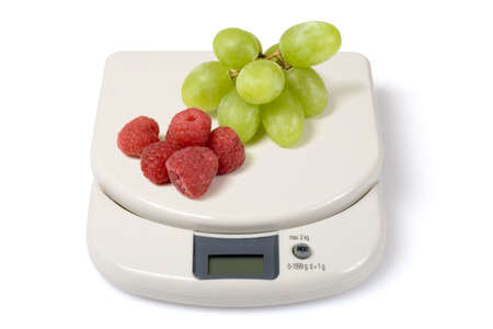 serie: Scale with raspberries and grapes isolated over a white background. Check other photos in the serie.