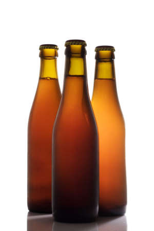 Three beer bottles in backlight isolated over a white background Stock Photo