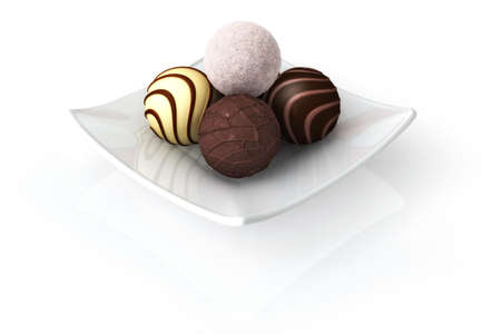 Chocolate truffles on a plate isolated over a white background. Stock Photo