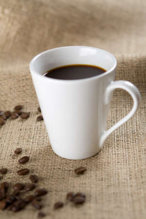 sackcloth: White coffee cup with roasted coffee beans on sackcloth. Shallow depth of field. Stock Photo