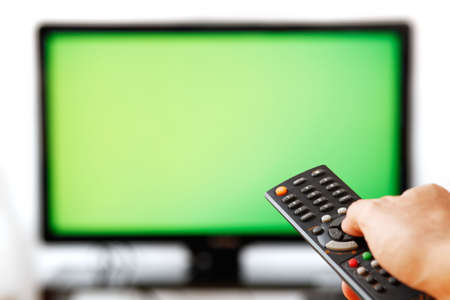Out of focus TV LCD set and remote control in mans hand isolated over a white background. Blank screen.