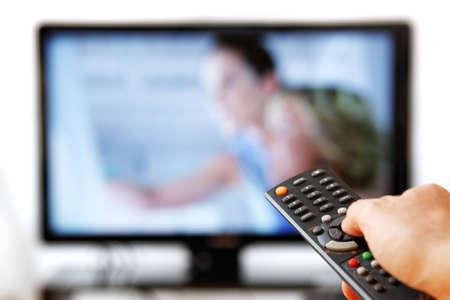 viewing: Out of focus TV LCD impostare e telecomando in mano dell'uomo isolato su uno sfondo bianco. Archivio Fotografico