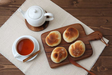 baked white bread tea cup on wood cutting board isolated on table 写真素材 - 124721295