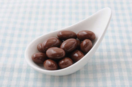 a heap of chocolate covered almonds on a plate on tablecloth