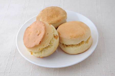 plain scone biscuit on a plate on tablecloth