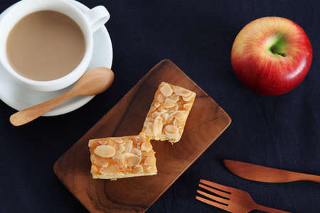 piece of Almond Apple Pound Cake on cutting board and milk coffee on wood table