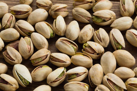 spread of pistachio with shells on wood table