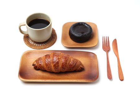 croissant french bread on wood plate and hot coffee with dessert isolated on white background 写真素材