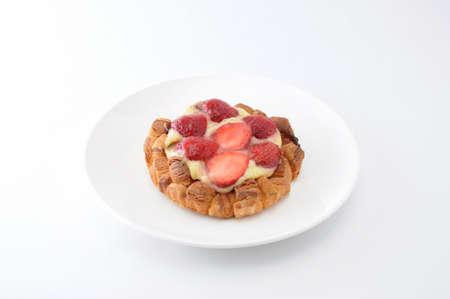 Gâteau aux fraises avec crème pâtissière sur une assiette sur fond blanc
