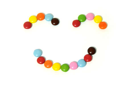 smiley of colorful chocolate candy on white background
