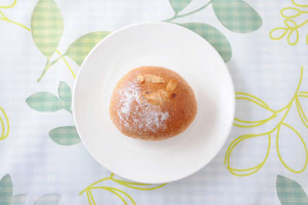 butter bread roll on a plate on tablecloth