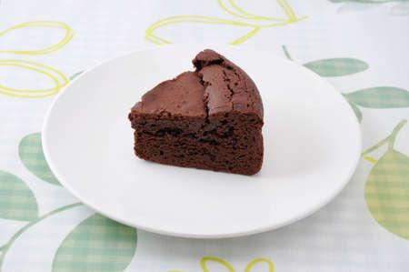 piece of chocolate cake gateau chocola on a plate on table cloth
