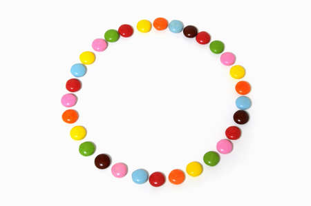 circle of colorful chocolate candies spread on white background Reklamní fotografie