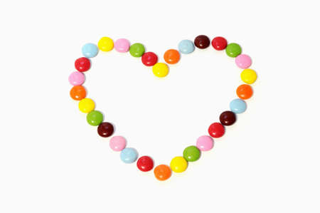 heart of colorful chocolate candy spread on white background