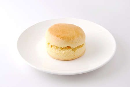plain scone biscuit isolated on a plate on white background
