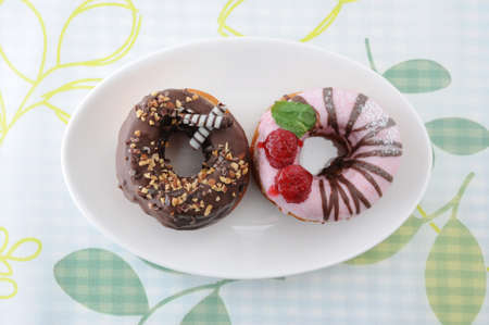 sweet chocolate almond and strawberry cake doughnuts on a plate on tablecloth