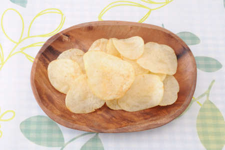potato chips on wood plate on table cloth