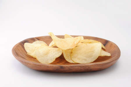 potato chips on wood plate on white background Stock Photo