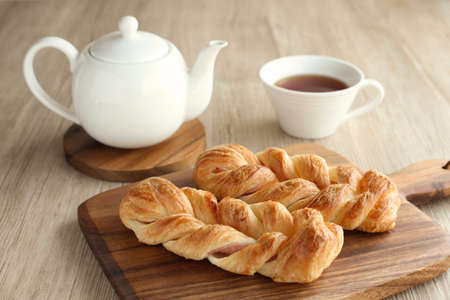 ham danish bread with tea pot and tea cup on table