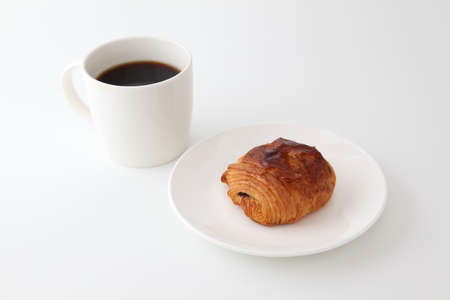 french bread pain au chocolat chocolate croissant on plate with cup of coffee on white background