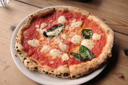 pizza margherita di napoli su piastra su tavola di legno