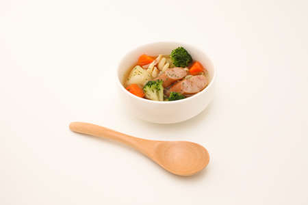 pot-au-feu vegetables sausage soup isolated wood spoon on white background