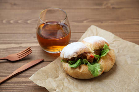 fried chicken hamburger lettuce on brown paper isolated on wooden table