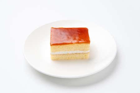 orange honey syrup cake on plate isolated on white background