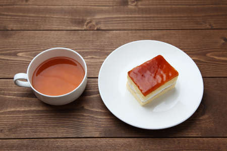 orange honey syrup cake on plate with hot tea isolated on table