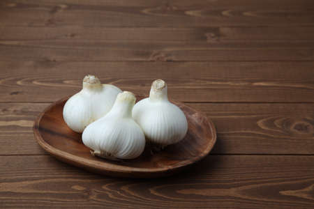 raw garlic on wooden plate isolated on table