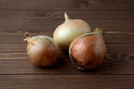 raw onions isolated on wooden table