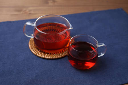 cup of tea and tea pot isolated on wooden table