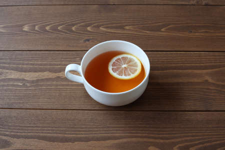 cup of tea with sliced lemon isolated on wooden table