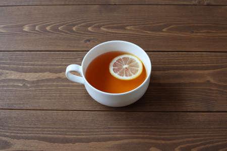 Tasse Tee mit Zitronenscheiben isoliert auf Holztisch