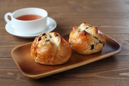 raisin bread with English tea isolated on wooden table