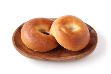 plain bagels bread on wooden plate on white background