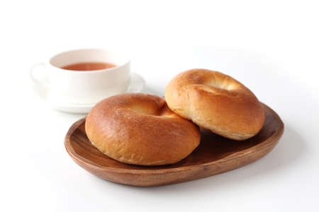 plain bagels bread on wooden plate with hot tea on white background 写真素材